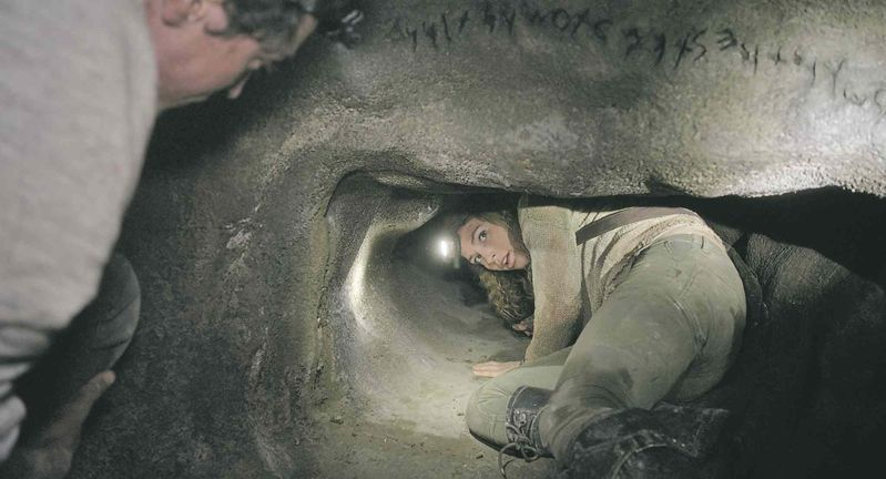 """Scarlett enters a tunnel underneath the inscription """"abandon hope all ye who enter here"""""""